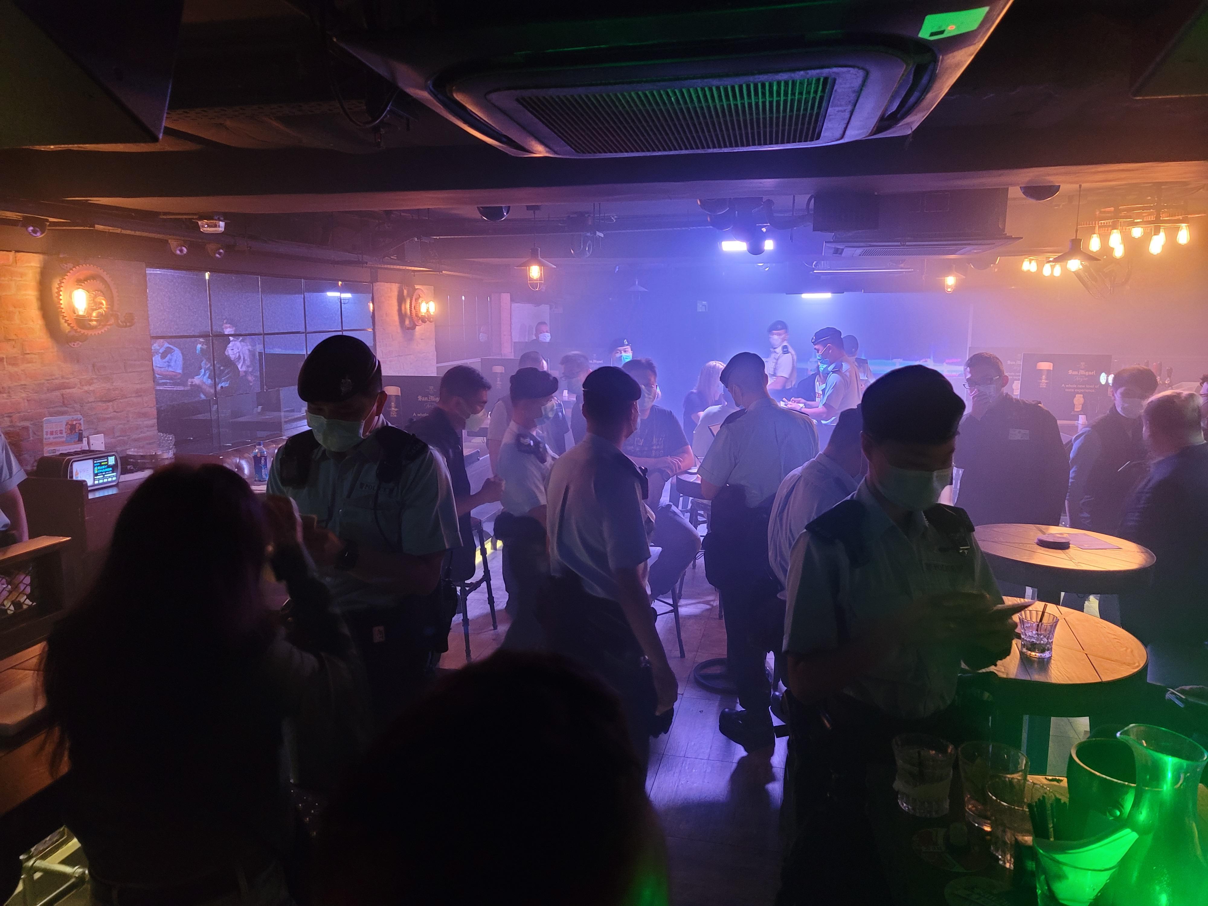 警員在酒吧檢查及作登記。(點新聞記者何燊亮攝)