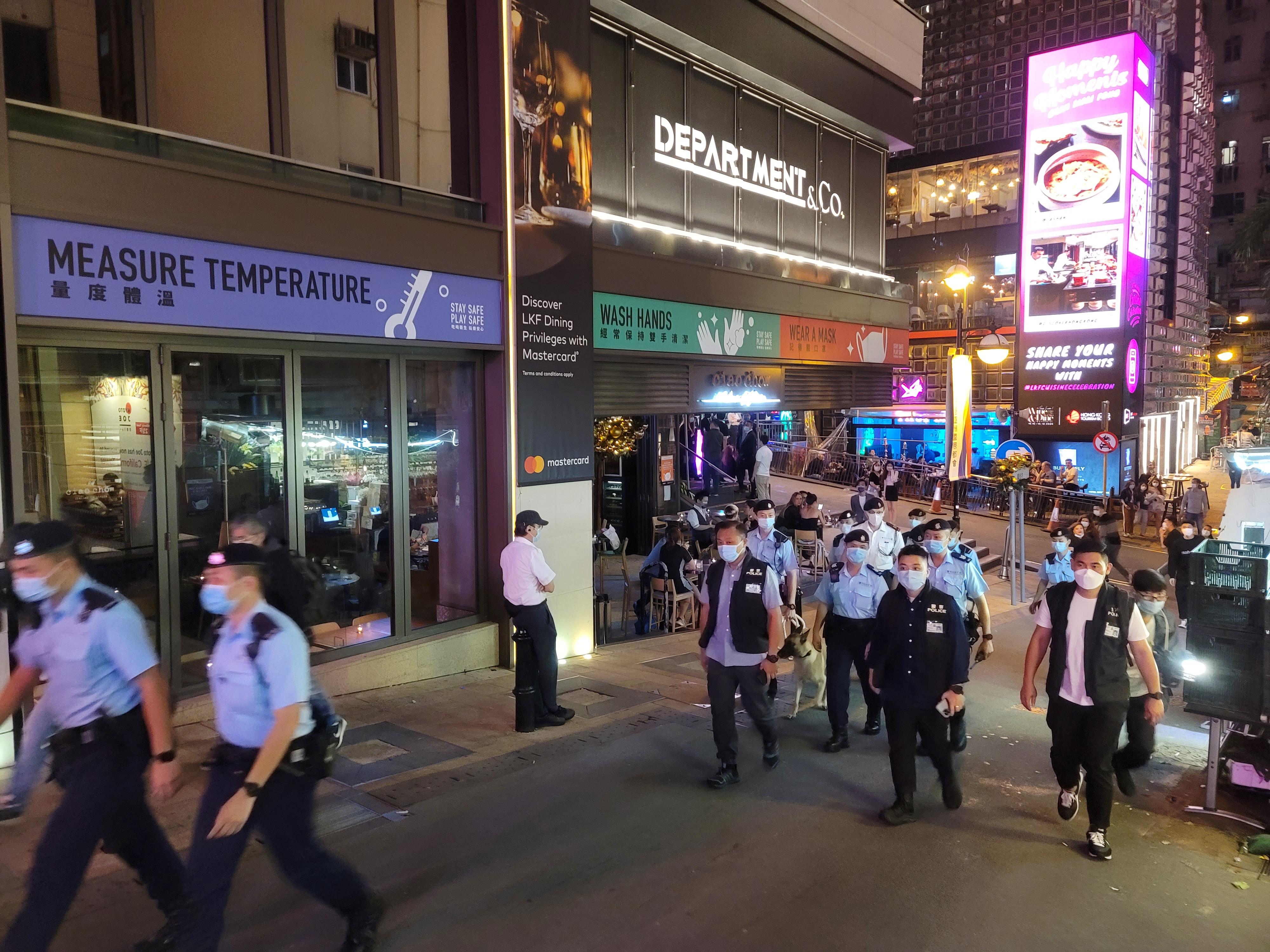 政府日前對餐飲場所,包括酒吧收緊防疫措施。警方及食環署將加強相關巡查。圖為警方今晚到中環蘭桂坊酒吧區查牌。(點新聞記者何燊亮攝)